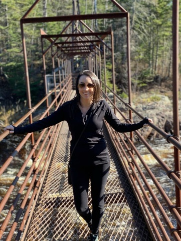 Jayme Kolbo standing on a foot bridge